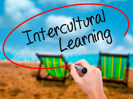 Man Hand writing Intercultural Learning with black marker on visual screen. Isolated on sunbed on the beach. Business, technology, internet concept. Stock Photo