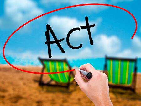 Man Hand writing Act  with black marker on visual screen. Isolated on sunbed on the beach. Business, technology, internet concept. Stock Photo