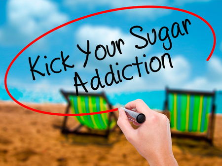 Man Hand writing Kick Your Sugar Addiction with black marker on visual screen. Isolated on sunbed on the beach. Business, technology, internet concept. Stock Photo
