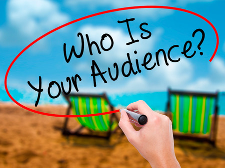 relevance: Man Hand writing Who Is Your Audience? with black marker on visual screen. Isolated on sunbed on the beach. Business, technology, internet concept. Stock Image Stock Photo