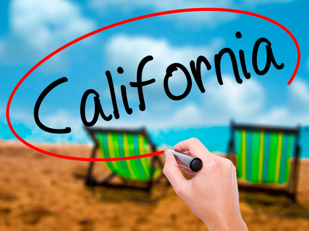 Man Hand writing California with black marker on visual screen. Isolated on sunbed on the beach. Business, technology, internet concept. Stock Image