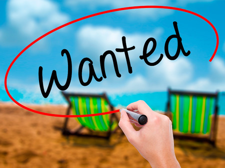 Man Hand writing Wanted with black marker on visual screen. Isolated on sunbed on the beach. Business, technology, internet concept. Stock Photo