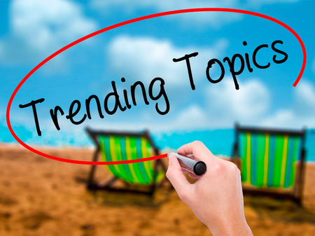 topics: Man Hand writing Trending Topics with black marker on visual screen. Isolated on sunbed on the beach. Business, technology, internet concept. Stock Photo Stock Photo