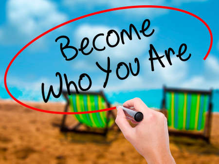 Man Hand writing Become Who You Are with black marker on visual screen. Isolated on sunbed on the beach. Business, technology, internet concept. Stock Photo Stock Photo