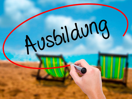 Man Hand writing Ausbildung (Education in German) with black marker on visual screen. Isolated on sunbed on the beach. Business, technology, internet concept. Stock Photo Stock Photo