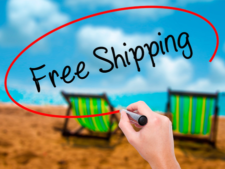 Man Hand writing Free Shipping with black marker on visual screen. Isolated on sunbed on the beach. Business, technology, internet concept. Stock Photo
