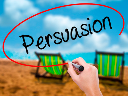 Man Hand writing Persuasion with black marker on visual screen. Isolated on sunbed on the beach. Business, technology, internet concept. Stock Photo