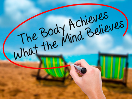 believes: Man Hand writing The Body Achieves What the Mind Believes with black marker on visual screen. Isolated on sunbed on the beach. Business, technology, internet concept. Stock Photo Stock Photo