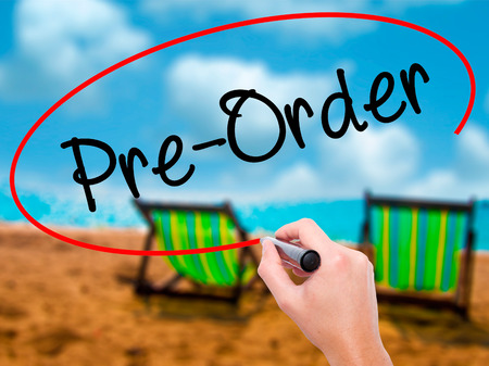 preorder: Man Hand writing Pre-Order  with black marker on visual screen. Isolated on sunbed on the beach. Business, technology, internet concept. Stock Photo