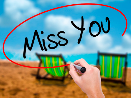 Man Hand writing Miss You with black marker on visual screen. Isolated on sunbed on the beach. Business,  technology, internet concept. Stock Photo
