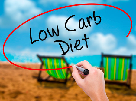 vegetable carbon: Man Hand writing Low Carb Diet with black marker on visual screen. Isolated on sunbed on the beach. Business, technology, internet concept. Stock Photo Stock Photo