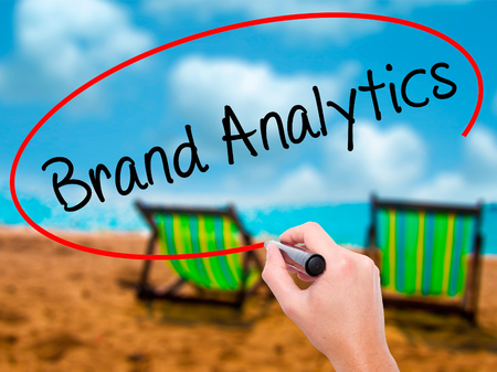 brand monitoring: Man Hand writing Brand Analytics with black marker on visual screen. Isolated on sunbed on the beach. Business, technology, internet concept. Stock Photo