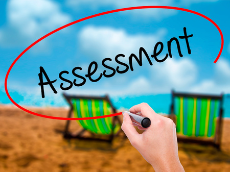 Man Hand writing Assessment with black marker on visual screen. Isolated on sunbed on the beach. Business, technology, internet concept. Stock Photo