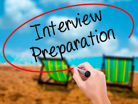 job qualifications: Man Hand writing Interview Preparation with black marker on visual screen. Isolated on sunbed on the beach. Business, technology, internet concept. Stock Photo