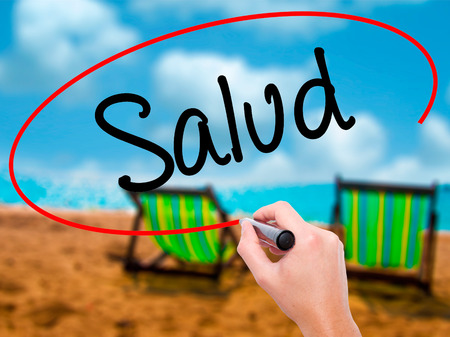 Man Hand writing Salud (Health in Spanish) with black marker on visual screen. Isolated on sunbed on the beach. Business, technology, internet concept. Stock Photo