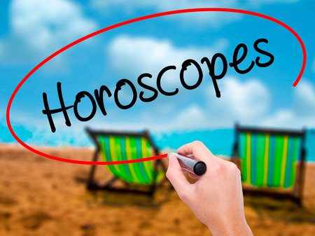 Man Hand writing Horoscopes  with black marker on visual screen. Isolated on sunbed on the beach. Business, technology, internet concept. Stock Photo