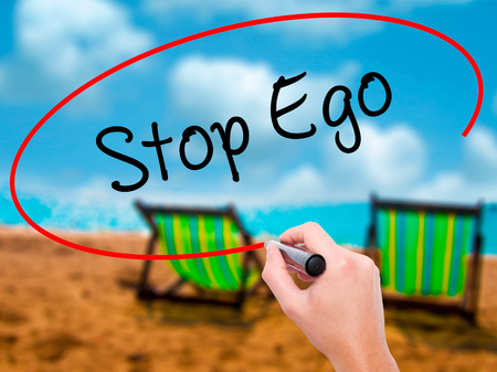 Man Hand writing  Stop Ego with black marker on visual screen. Isolated on sunbed on the beach. Business, technology, internet concept. Stock Photo