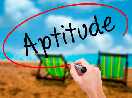 aptitude: Man Hand writing Aptitude with black marker on visual screen. Isolated on sunbed on the beach. Business, technology, internet concept. Stock Photo