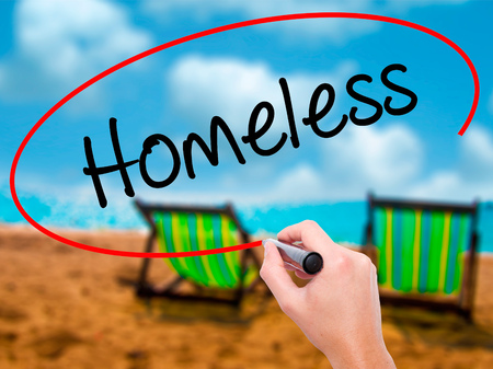 Man Hand writing Homeless with black marker on visual screen. Isolated on sunbed on the beach. Business, technology, internet concept. Stock Photo
