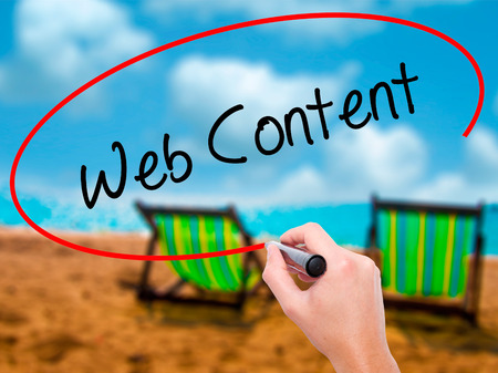 Man Hand writing Web Content with black marker on visual screen. Isolated on sunbed on the beach. Business, technology, internet concept. Stock Photo