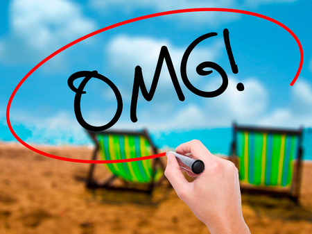 disbelief: Man Hand writing OMG (Oh My God) with black marker on visual screen. Isolated on sunbed on the beach. Business, technology, internet concept.
