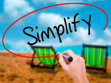 Man Hand writing Simplify with black marker on visual screen. Isolated on sunbed on the beach. Business, technology, internet concept. Stock Photo Stock Photo