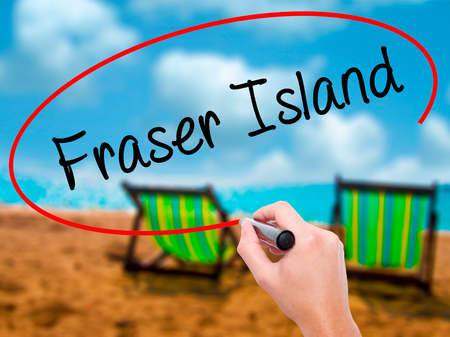 fraser island: Man Hand writing Fraser Island with black marker on visual screen. Isolated on sunbed on the beach. Business, technology, internet concept. Stock  Photo