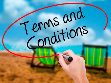 Man Hand writing Terms and Conditions with black marker on visual screen. Isolated on sunbed on the beach. Business, technology, internet concept. Stock Photo Stock Photo