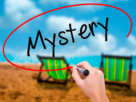 inference: Man Hand writing Mystery with black marker on visual screen. Isolated on sunbed on the beach. Business, technology, internet concept. Stock Photo Stock Photo