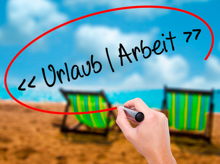 arbeit: Man Hand writing Uralaub Arbeit (Vacation - Work in German)  with black marker on visual screen. Isolated on sunbed on the beach. Business, technology, internet concept. Stock Photo