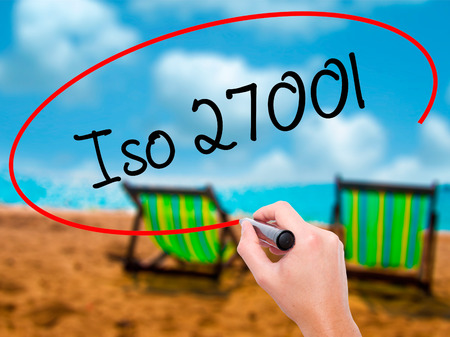 Man Hand writing Iso 27001  with black marker on visual screen. Isolated on sunbed on the beach. Business, technology, internet concept. Stock Photo