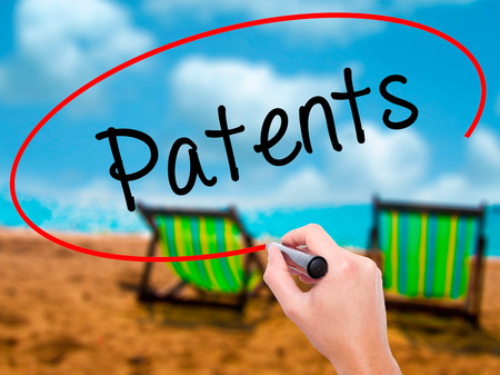 Man Hand writing Patents with black marker on visual screen. Isolated on sunbed on the beach. Business, technology, internet concept. Stock Photo Stock Photo