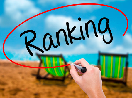 Man Hand writing Ranking with black marker on visual screen. Isolated on sunbed on the beach. Business, technology, internet concept. Stock Photo Stock Photo