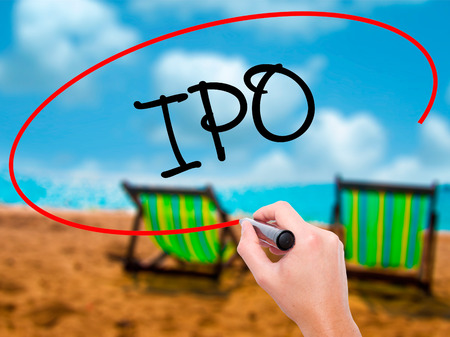 Man Hand writing IPO (Initial Public Offering)   with black marker on visual screen. Isolated on sunbed on the beach. Business, technology, internet concept. Stock Photo Stock Photo