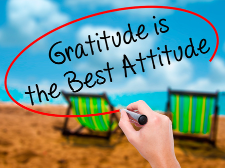 universal love: Man Hand writing Gratitude is the Best Attitude with black marker on visual screen. Isolated on sunbed on the beach. Business, technology, internet concept. Stock Photo