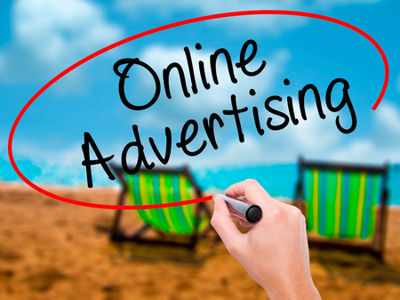Man Hand writing Online Advertising with black marker on visual screen. Isolated on sunbed on the beach. Business, technology, internet concept. Stock Image