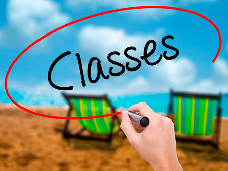Man Hand writing Classes   with black marker on visual screen. Isolated on sunbed on the beach. Business, technology, internet concept. Stock Photo