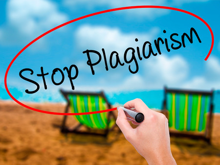 plagiarism: Man Hand writing Stop Plagiarism with black marker on visual screen. Isolated on sunbed on the beach. Business, technology, internet concept. Stock Photo