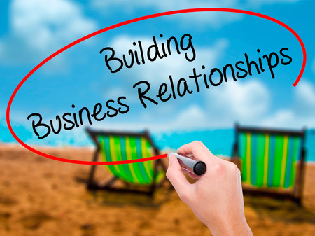 Man Hand writing  Building Business Relationships  with black marker on visual screen. Isolated on sunbed on the beach. Business, technology, internet concept. Stock Photo