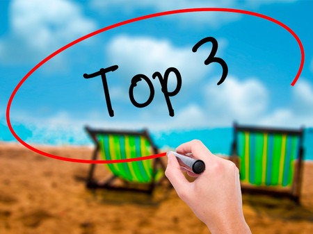 importance: Man Hand writing Top 3 with black marker on visual screen. Isolated on sunbed on the beach. Business, technology, internet concept.
