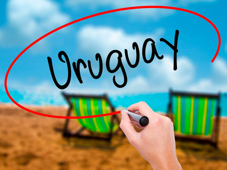 Man Hand writing Uruguay  with black marker on visual screen. Isolated on sunbed on the beach. Business, technology, internet concept. Stock Photo Stock Photo