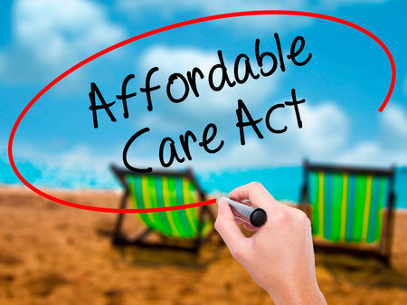 affordable: Man Hand writing Affordable Care Act with black marker on visual screen. Isolated on sunbed on the beach. Business, technology, internet concept. Stock Photo Stock Photo