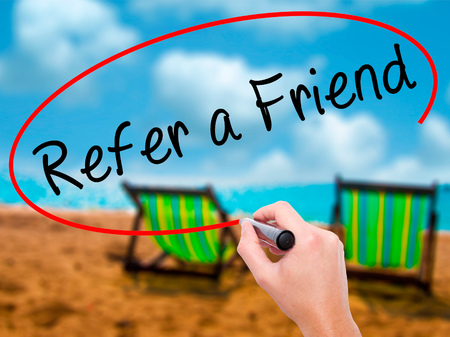 Man Hand writing Refer a Friend  with black marker on visual screen. Isolated on sunbed on the beach. Business, technology, internet concept. Stock Image