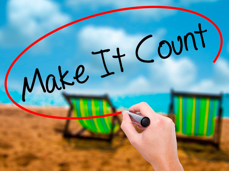 importance: Man Hand writing Make It Count with black marker on visual screen. Isolated on sunbed on the beach. Business, technology, internet concept. Stock Photo