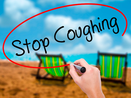 Man Hand writing Stop Coughing with black marker on visual screen. Isolated on sunbed on the beach. Business, technology, internet concept. Stock Photo
