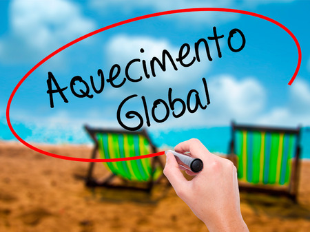Man Hand writing Aquecimento Global (Global Warming in Portuguese) with black marker on visual screen. Isolated on sunbed on the beach. Business, technology, internet concept. Stock Photo