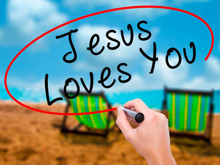 testament schreiben: Man Hand writing Jesus Loves You with black marker on visual screen. Isolated on sunbed on the beach. Religion, technology, internet concept. Stock Image Lizenzfreie Bilder