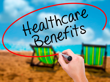 nhs: Man Hand writing Healthcare Benefits with black marker on visual screen. Isolated on sunbed on the beach. Business, technology, internet concept. Stock Photo