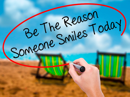 someone: Man Hand writing Be The Reason Someone Smiles Today  with black marker on visual screen. Isolated on sunbed on the beach. Business, technology, internet concept. Stock Photo Stock Photo