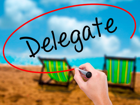 delegar: Man Hand writing Delegate with black marker on visual screen. Isolated on sunbed on the beach. Business, technology, internet concept. Stock Photo